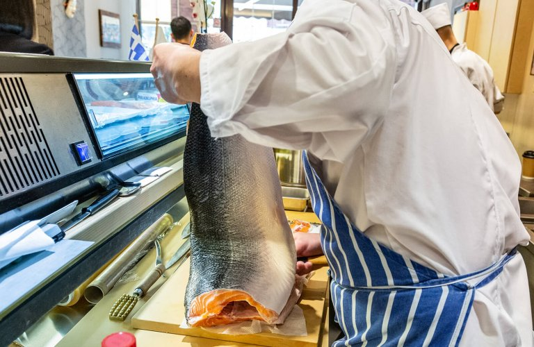 huge salmon being carved in a restaurant kitchen
